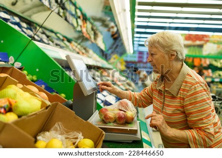 Elderly woman weighing goods on digital weight in supermarket, shopping for fruits and vegetables in produce department of a grocery store/supermarket ( color toned image ) - stock photo