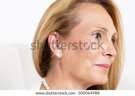 Elderly woman with a deaf-aid - stock photo
