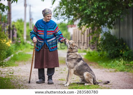 Elderly woman with a dog in countryside - stock photo