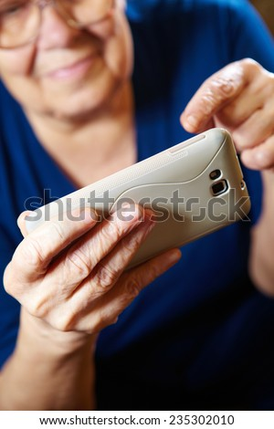 Elderly woman with a smartphone. Senior people using internet - stock photo