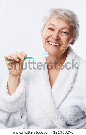 Elderly woman with a toothbrush on white background