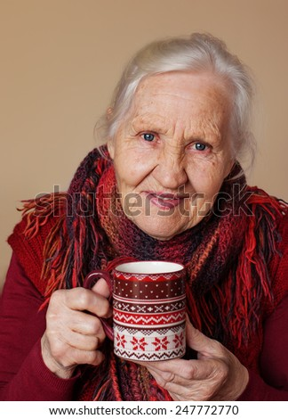 Elderly woman with cup of hot tea - stock photo