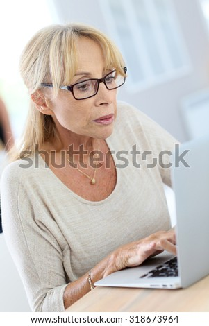 Elderly woman with eyeglasses using laptop computer