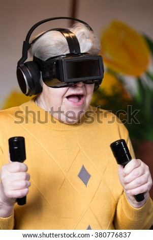 elderly woman with gaming simulator and controller is looking surprised