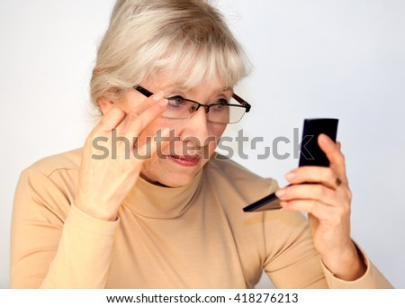 Elderly woman with glasses looks in the mirror