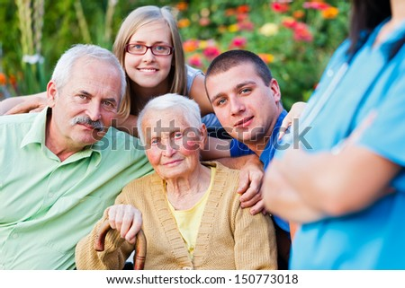 Elderly woman with her family supervised by a doctor.