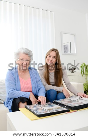 elderly woman with her young granddaughter at home looking at memory in family photo album - stock photo