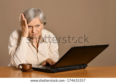 Elderly woman with laptop at the table