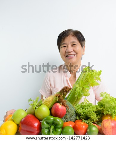 Elderly woman with pile of vegetables and fruits