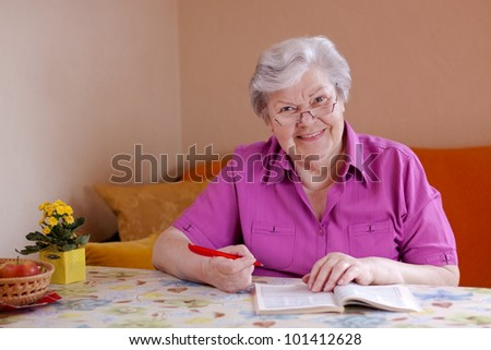 elderly woman with reading glasses sitting on the couch and smiles - stock photo