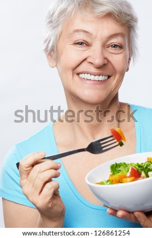 Elderly woman with salad on white background - stock photo