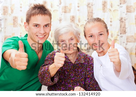 Elderly woman with the sweet young doctors - stock photo