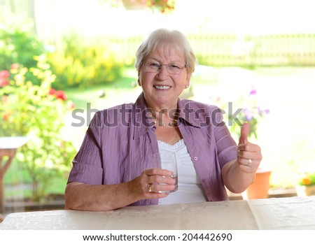 elderly woman with water glass and thumb up - stock photo