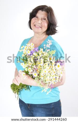 Elderly woman with wildflowers.  - stock photo