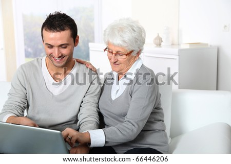 Elderly woman with young man using internet at home - stock photo