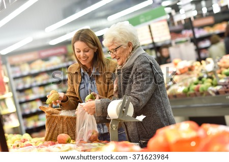 Elderly woman with young woman at the grocery store - stock photo