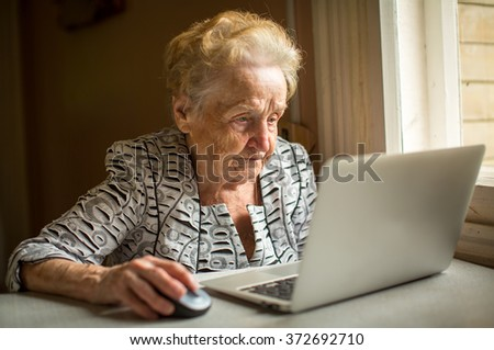 Elderly woman working on laptop at home sitting at the table. - stock photo