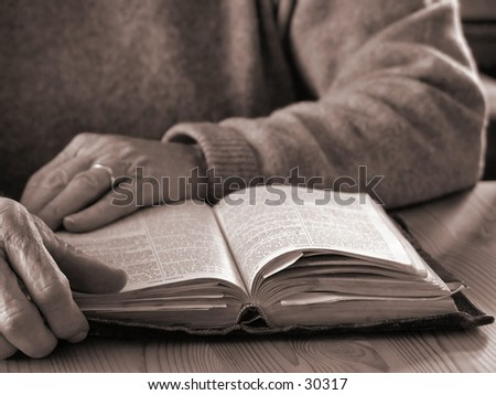 Elderly womans hands and Bible - stock photo