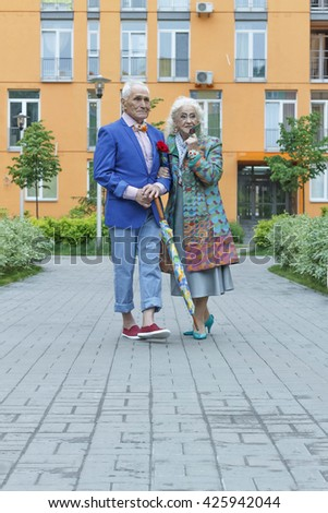 Elderly women takes a walk with the elderly man. Bright clothes, a festive makeover. - stock photo