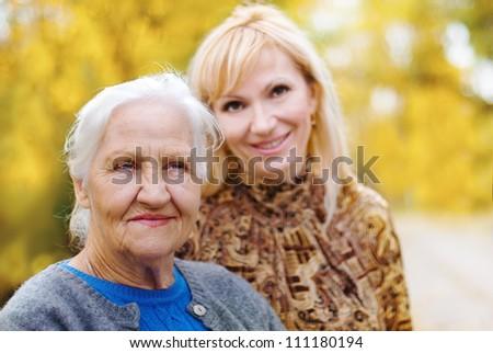 Elderly women with daughter in a garden - stock photo
