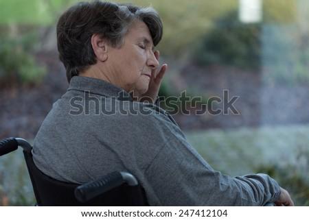 Elderly worried lady in nursing home - stock photo