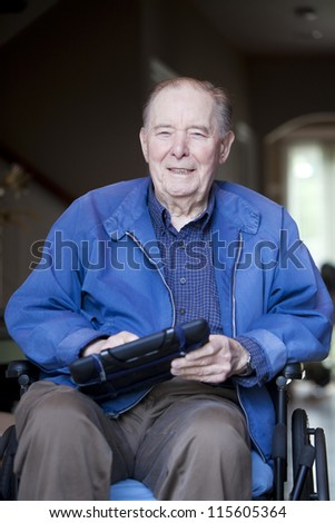 Elderly 90 yr old man in wheelchair holding tablet computer - stock photo