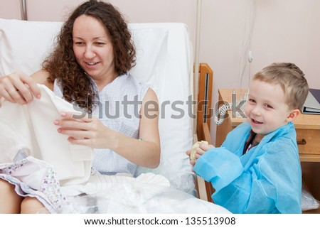 Eldest son with his mom consider clothes for newborn baby in maternity hospital
