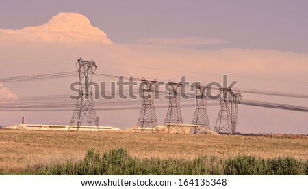 Electical Lines in Grassland Landscape on a Hot Summer Afternoon and Stormy Clouds   - stock photo