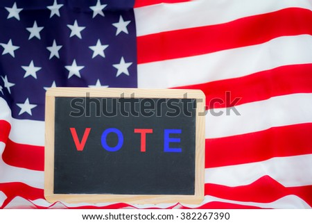 Election days in USA - Blackboard with american flag on background - Focus on blackboard - stock photo