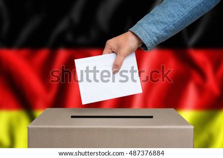 Election in Germany. The hand of woman putting her vote in the ballot box. German flag on background.