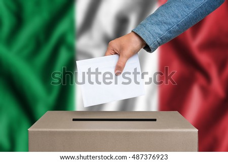 Election in Italy. The hand of woman putting her vote in the ballot box. Italian flag on background.