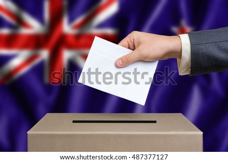 Election in New Zeland. The hand of man putting his vote in the ballot box. New Zeland flag on background.