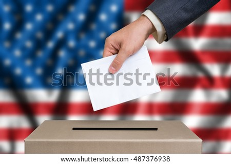 Election in United States of America. The hand of man putting his vote in the ballot box. American flag on background.