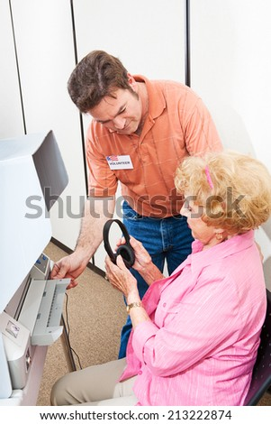 Election volunteer helps a hearing impaired senior woman vote on a touch screen machine using headphones.   - stock photo