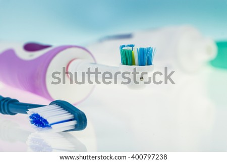 Electric and classic toothbrush on reflective surface and light blue background.
