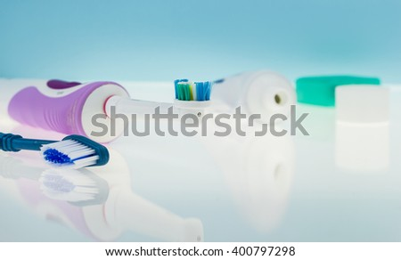 Electric and classic toothbrushes on reflective surface and light blue background. - stock photo