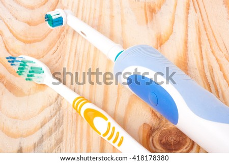 electric and manual toothbrushes on the wooden background - stock photo