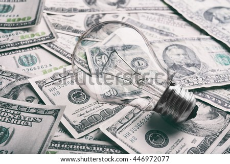 Electric bulb on dollars background