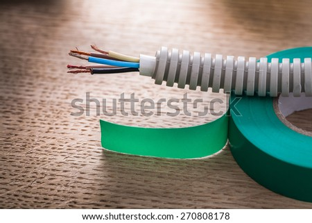 electric cable in corrugated pipe on roll of green insulating tape  - stock photo
