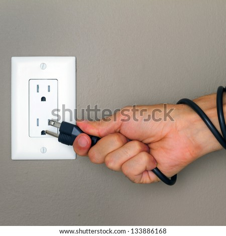 Electric cable on the hand and Electrical Outlet on the Wall. Power 110v - stock photo