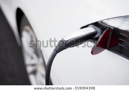 Electric car and its charger  - stock photo