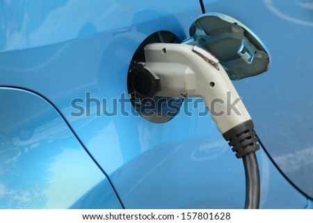 Electric Car Being Charged. Charging an electric car with the power supply plugged in.  - stock photo