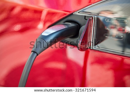electric car charging process by power cable supply plugged in - stock photo