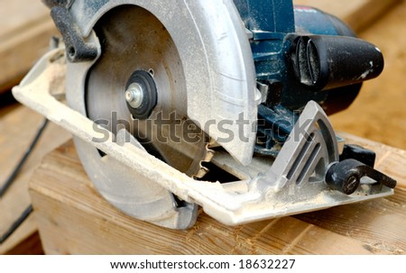 Electric circular saw over wood with sawdust