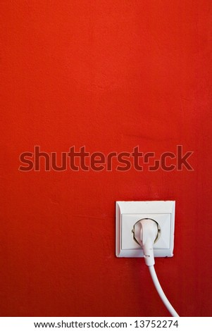 electric consumption - electric outlet on red wall - stock photo
