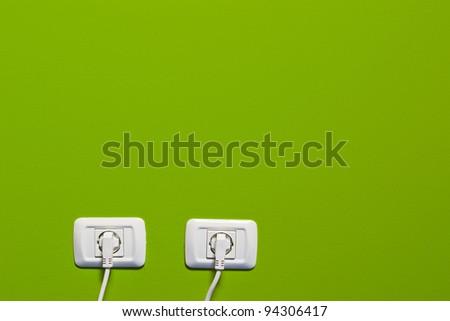 electric consumption - two socket on green wall - stock photo