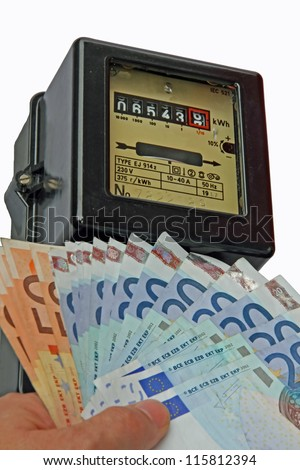 electric current meter with many euro to be paid and a hand that holds them - stock photo