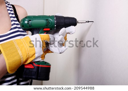Electric drill touching wall, action concept - stock photo