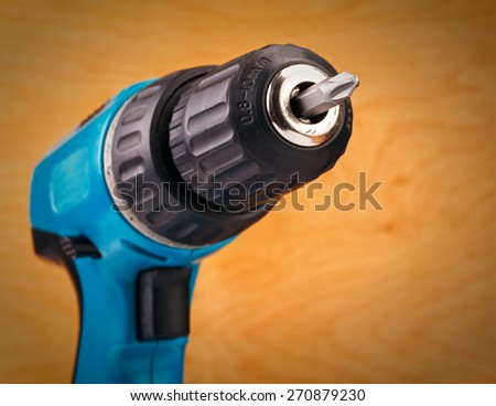 electric drill with drill bit on a wooden background - stock photo