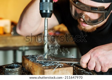 Electric drilling machine with manual pressure, a man holding a metal part and the hole is drilled, strongly pressing drill to the workpiece surface - stock photo